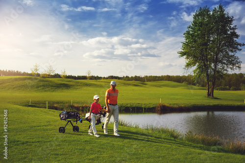 Cadres-photo bureau Golf Father with son at golf field