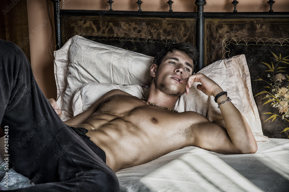 Fototapeta Shirtless sexy male model lying alone on his bed