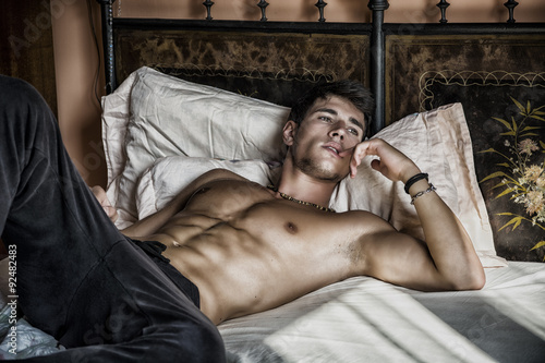 Shirtless sexy male model lying alone on his bed Tablou Canvas