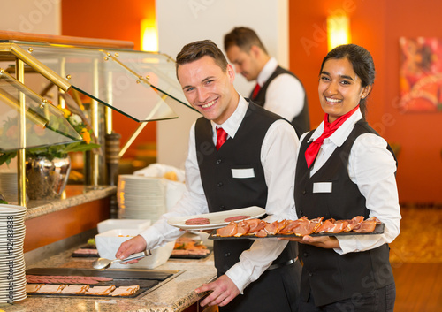Fotografie, Obraz  Catering service employees filling buffet at restaurant or hotel