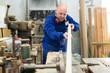 Artisan shaping timber at factory
