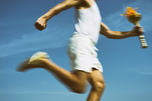 Torchbearer In Old Fashioned White Uniform Running With Sport Torch In Motion Blur Across Sunny Blue Sky