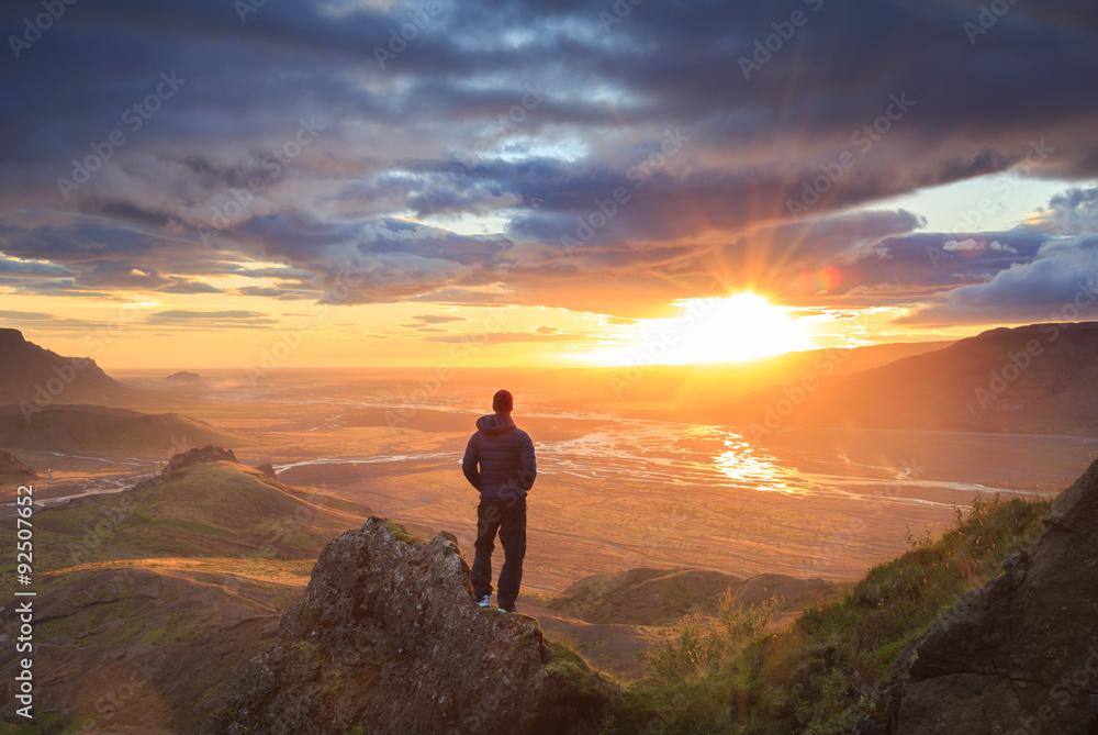 Fototapety, obrazy: Hiker standing on a ledge of a mountain, enjoying the beautiful sunset over a wide river valley in Thorsmork, Iceland.