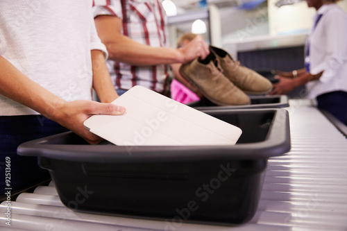 Man Puts Digital Tablet Into Tray For Airport Security Check Poster