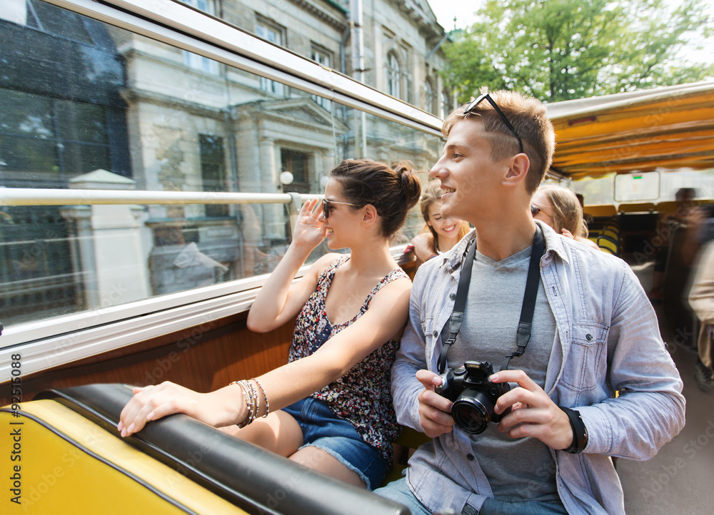 Fototapeta smiling couple with camera traveling by tour bus