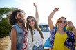 happy young hippie friends dancing outdoors
