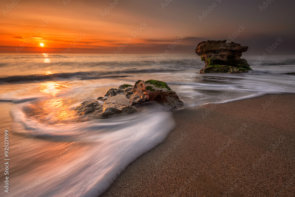 Fototapeta Sea sunrise. Stormy sea beach with slow shutter and waves flowing out