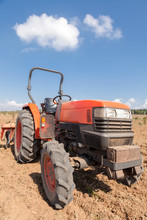 Small Red Tractor With Plow In Field. Cloudy Sky