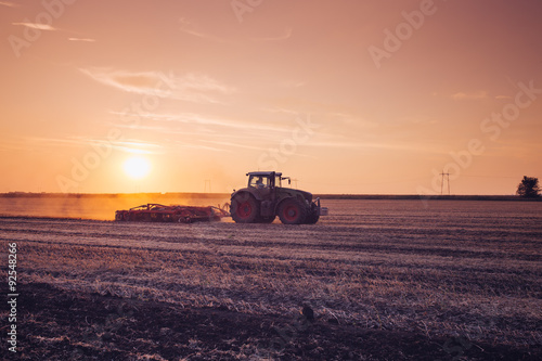 Fotografia  Tractor on the field by sunset.