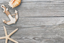 Small Anchor And Seashells On Wooden Background