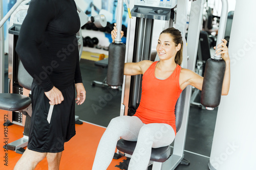 Young male trainer giving instructions to a woman in a gym Poster