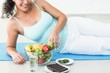 Smiling pregnant woman lying by fruits and chocolates