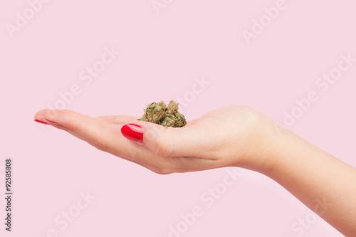 Photo  Woman holding cannabis bud.