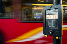 Pedestrians Wait! A UK Pedestrian Crossing Sign With A Motion Blurred London Bus Background.