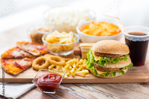 close up of fast food snacks and drink on table © Syda Productions