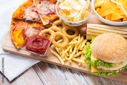 close up of fast food snacks on wooden table © Syda Productions