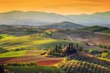 Krajobraz Toskanii o wschodzie słońca. Gospodarstwo wiejskie w Toskanii, winnica, wzgórza.
