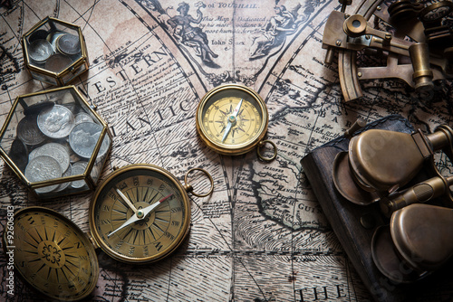 Photo Old compass, astrolabe on vintage map. Retro style.
