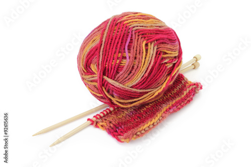 Fotografie, Obraz  Ball of colorful yarn, wooden knitting needles, and a piece of hand knitted textile