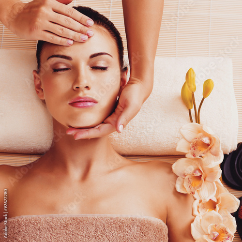 Masseur doing massage the head of an woman in spa salon