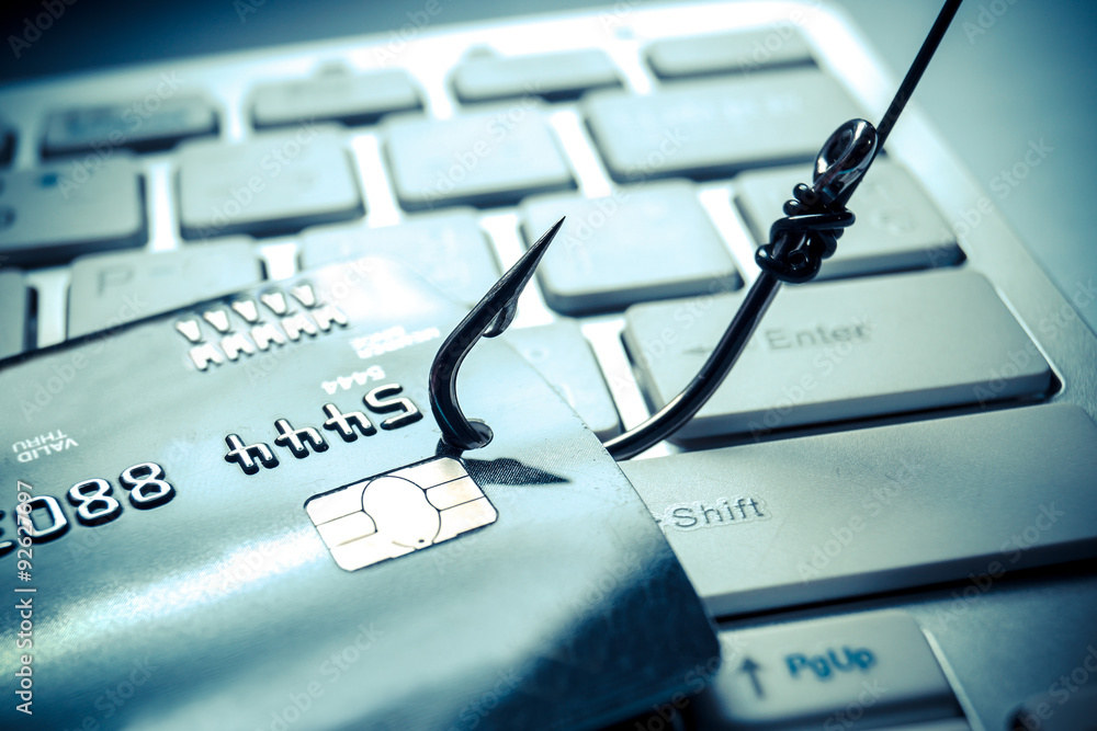 Fototapeta credit card phishing - piles of credit cards with a fish hook on computer keyboard