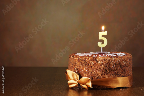 Photographie  Gâteau d'anniversaire au chocolat avec bougie brûlant comme un numéro cinq s