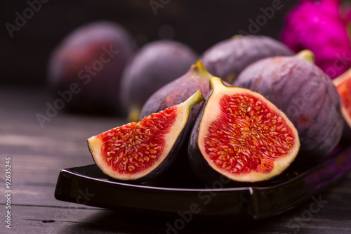 Stampa su Tela Ripe delicious figs and autumn flowers on black wooden background