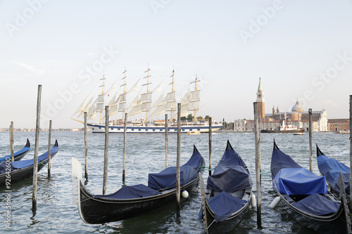 In the foreground several gondolas in the background a huge tourist sailing ship crossing the Venetian lagoon, Italy