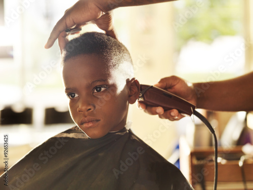 little boy getting his head shaved by barber Poster