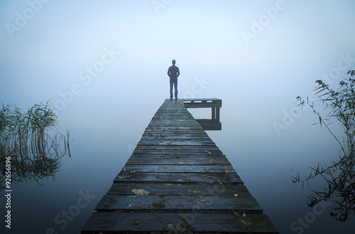 Man standing on a jetty at a lake during a foggy, gray morning.