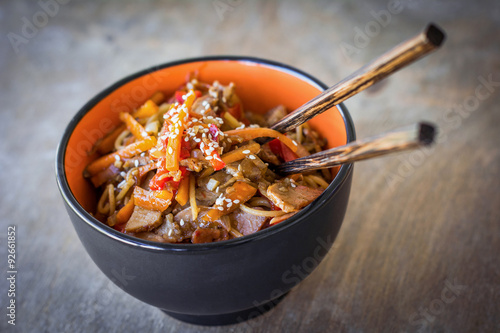 Fotografering Stir fry with vegetables and meat garnished with sesame seeds in bowl with chopsticks