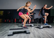 Leinwanddruck Bild - Woman trainer doing aerobic class with steppers in gym