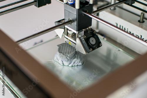 Photo  Imprimante 3D en cours d'impression d'un Yoda en résine grise au Fab Lab de la C