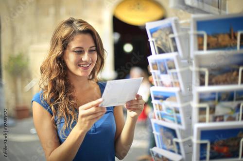 Fotografia  Happy woman choosing a postcard