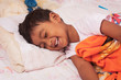 a little asian boy laughing on the bed