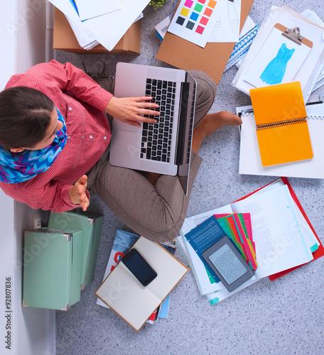 Fototapeta Student with books spread around working on a laptop obraz na płótnie