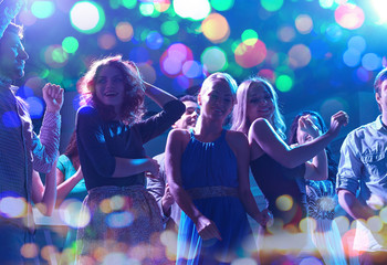 Fototapeta group of happy friends dancing in night club