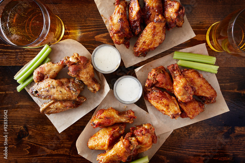Tuinposter Kip overhead view of four different flavored chicken wings with ranch dressing, beer, and celery sticks