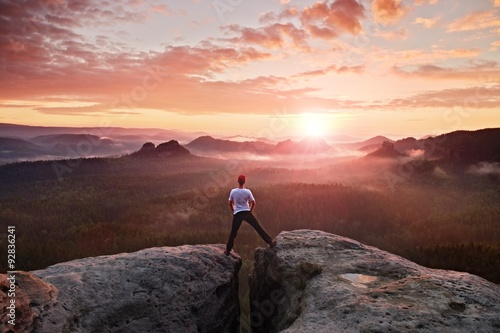 Fototapeta Crazy jumping hiker in black celebrate triumph between two rocky peaks above mist