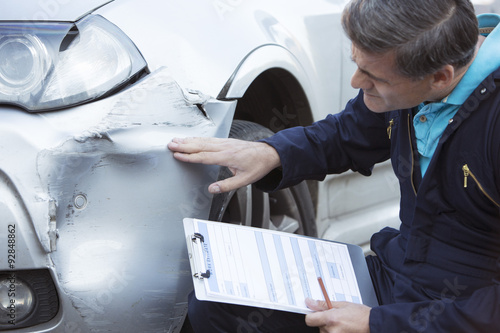 Foto  Auto Workshop Mechanic Inspecting Damage To Car And Filling In R