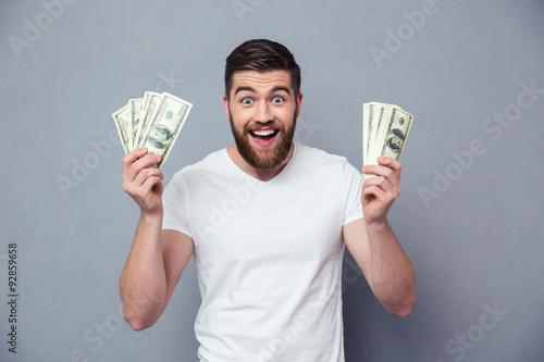 Fototapeta Cheerful man holding dollar bills obraz