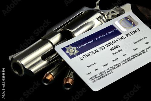 Fotografía  Revolver y balas y permiso de arma oculta