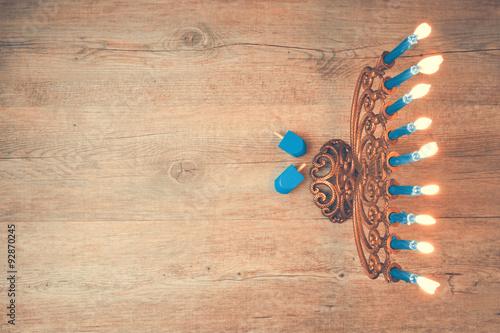 Zdjęcie XXL Żydowskie święto Chanuka kreatywne tło z menorą. Widok z góry z naciskiem na menorah. Efekt retro filtra.