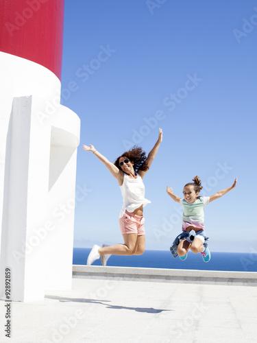 Fotografía  Madre e hija saltando contentas junto a faro