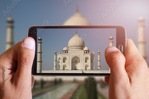 Male hand taking photo of Taj Mahal with cell, mobile phone Poster