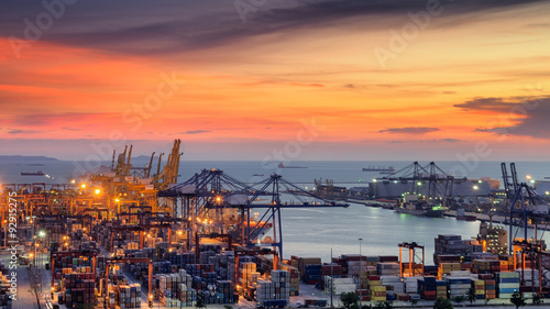 Fotografia, Obraz  Container Cargo freight ship with working crane bridge in shipyard at dusk for L