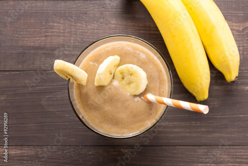 Recess Fitting Milkshake Banana smoothie and fresh banana on wooden background. Top view