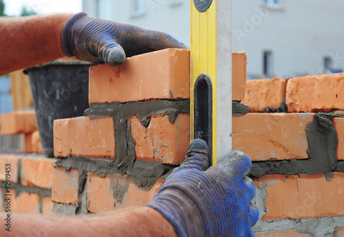 Láminas  Bricklayer Using a Spirit  Level to Check New  Red Brick Wall Outdoor