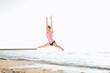 beautiful sporty woman jumping on seaside, gymnast female doing