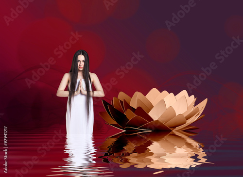 Woman in white dress beside lotus